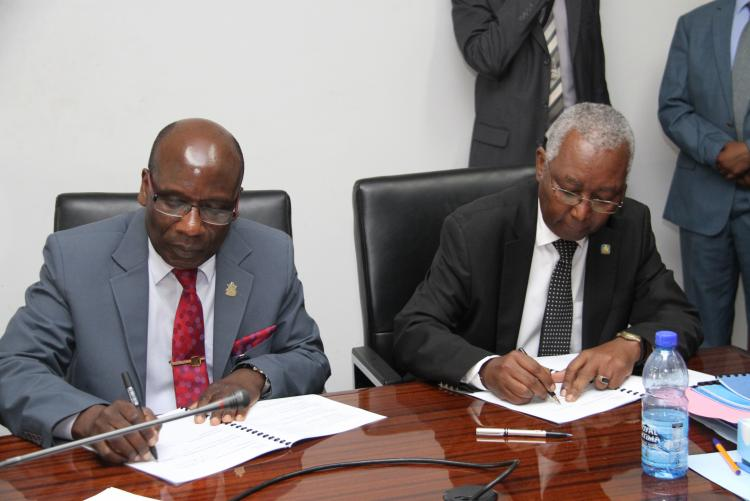 The Deputy Vice Chancellor Academic Affairs and the Academic Registrar signing the 2019/2020 Performance Contracting with the Vice-Chancellor